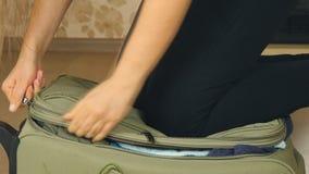 Mujer joven que se coloca en sus rodillas en la maleta sobrellenada, intentando cerrarla almacen de metraje de vídeo