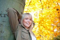 Mujer joven que se coloca en un árbol Foto de archivo libre de regalías