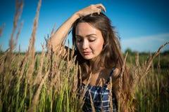 Mujer joven que se coloca en un campo de la hierba en día de verano fotos de archivo