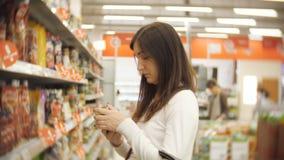 Mujer joven que se coloca en una botella de salsa de tomate en las manos de un supermercado metrajes