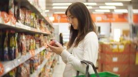 Mujer joven que se coloca en una botella de salsa de tomate en las manos de un supermercado almacen de video