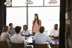 Mujer joven que se coloca en una reunión en una sala de reunión del negocio imagen de archivo