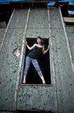 Mujer joven que se coloca en ventana Fotos de archivo