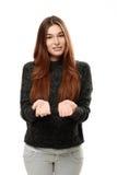 Mujer joven que se coloca que lleva a cabo su mano que muestra algo Fotografía de archivo