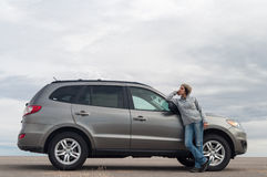 Mujer joven que se coloca que se inclina en el coche Fotografía de archivo