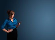 Mujer joven que se coloca y que mecanografía en su teléfono con el espacio de la copia fotografía de archivo libre de regalías