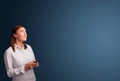 Mujer joven que se coloca y que mecanografía en su teléfono con el espacio de la copia Fotografía de archivo