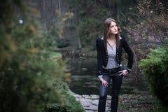 Mujer joven que se coloca y que presenta en el bosque Fotografía de archivo libre de regalías