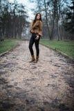 Mujer joven que se coloca y que presenta en el bosque Imágenes de archivo libres de regalías
