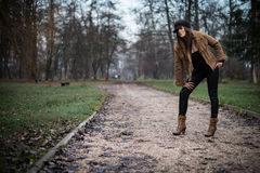 Mujer joven que se coloca y que presenta en el bosque Imagen de archivo libre de regalías
