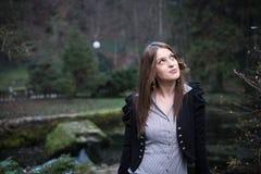 Mujer joven que se coloca y que presenta en el lago Fotos de archivo