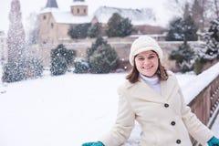 Mujer joven que se divierte con nieve el día de invierno Foto de archivo