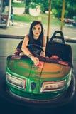 Mujer joven que se divierte en coche de parachoques eléctrico Fotos de archivo