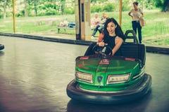 Mujer joven que se divierte en coche de parachoques eléctrico Imagen de archivo libre de regalías