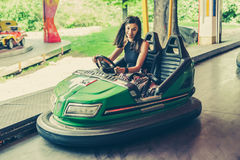 Mujer joven que se divierte en coche de parachoques eléctrico Fotografía de archivo