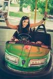 Mujer joven que se divierte en coche de parachoques eléctrico Fotos de archivo libres de regalías