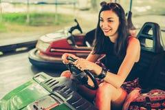 Mujer joven que se divierte en coche de parachoques eléctrico Imagenes de archivo