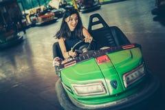 Mujer joven que se divierte en coche de parachoques eléctrico Imagen de archivo