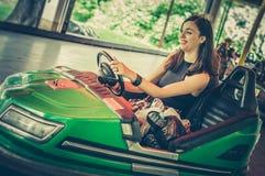 Mujer joven que se divierte en coche de parachoques eléctrico Foto de archivo