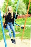 Mujer joven que se divierte que balancea en un día soleado Fotografía de archivo
