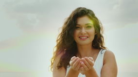 Mujer joven que se divierte, soplando en confeti en sus palmas, sonriendo Concepto de gente feliz metrajes