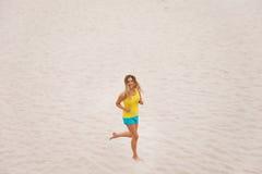 Mujer joven que se ejecuta en la playa Foto de archivo libre de regalías