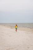 Mujer joven que se ejecuta en la playa Foto de archivo