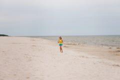 Mujer joven que se ejecuta en la playa Imagen de archivo