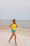 Mujer joven que se ejecuta en la playa Imagenes de archivo
