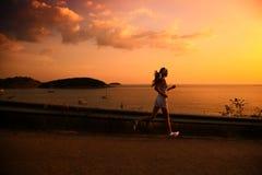Mujer joven que se ejecuta en la puesta del sol Imágenes de archivo libres de regalías