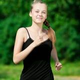 Mujer joven que se ejecuta en parque verde Fotografía de archivo libre de regalías