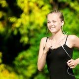 Mujer joven que se ejecuta en parque verde Foto de archivo libre de regalías