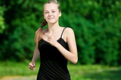 Mujer joven que se ejecuta en parque verde Foto de archivo