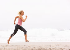 Mujer joven que se ejecuta a lo largo de la playa del invierno Imagen de archivo libre de regalías