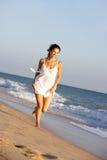 Mujer joven que se ejecuta a lo largo de la playa del verano Fotografía de archivo libre de regalías