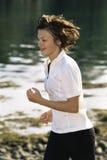 Mujer joven que se ejecuta a lo largo del borde del agua Foto de archivo libre de regalías