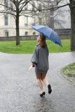 Mujer joven que se ejecuta a través de la lluvia Foto de archivo libre de regalías