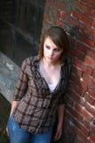 Mujer joven que se inclina contra la pared de ladrillo Imagen de archivo