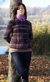 Mujer joven que se inclina contra un árbol en otoño Imágenes de archivo libres de regalías