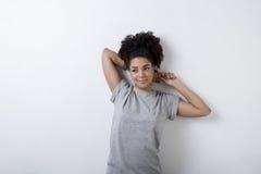 Mujer joven que se inclina contra una pared blanca imagenes de archivo