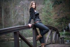Mujer joven que se inclina en el puente Imagenes de archivo