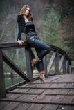Mujer joven que se inclina en el puente Fotografía de archivo