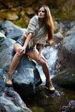 Mujer joven que se inclina en las rocas de la montaña imagenes de archivo