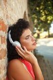 Mujer joven que se inclina en una pared de ladrillo que escucha la música Fotografía de archivo libre de regalías