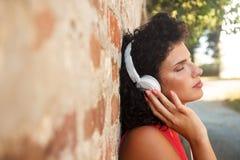 Mujer joven que se inclina en una pared de ladrillo que escucha la música Fotos de archivo