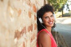 Mujer joven que se inclina en una pared de ladrillo que escucha la música Fotografía de archivo