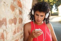 Mujer joven que se inclina en una pared de ladrillo que escucha la música Imagen de archivo libre de regalías