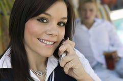 Mujer joven que se incorpora por la piscina en cierre del retrato del teléfono celular Imagenes de archivo