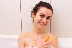 Mujer joven que se lava con la esponja en el baño Fotos de archivo