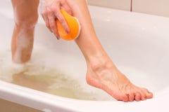 Mujer joven que se lava con la esponja en el baño Foto de archivo